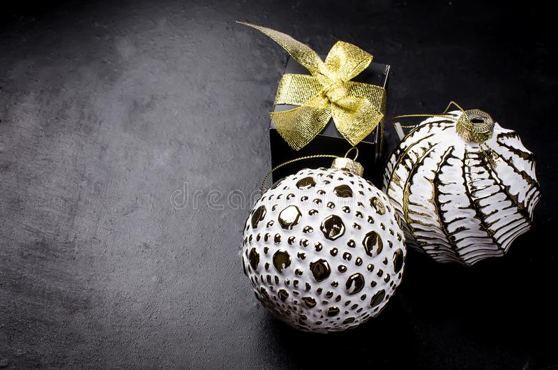 Elegant Christmas background with white retro balls and gifts. Two beautiful white and golden christmas balls and black gift box with gold ribbon on a black royalty free stock photos