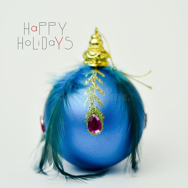 Elegant christmas ball and text happy holidays. Closeup of an elegant christmas ball ornamented with feathers and jewels on an off-white surface and the text royalty free stock image