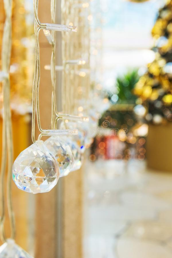 Elegant Christmas New Year decorations crystal balls sparkling in bokeh lights. Festive fir tree in the background stock photo