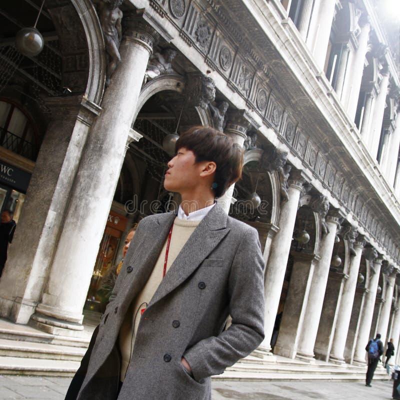 Elegant cinese man som går i gata i Venedig italy royaltyfri fotografi
