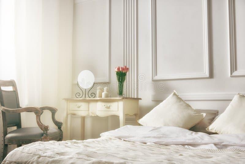 Elegant classic bedroom. Bedroom in soft light colors. big comfortable double bed in elegant classic bedroom stock photography