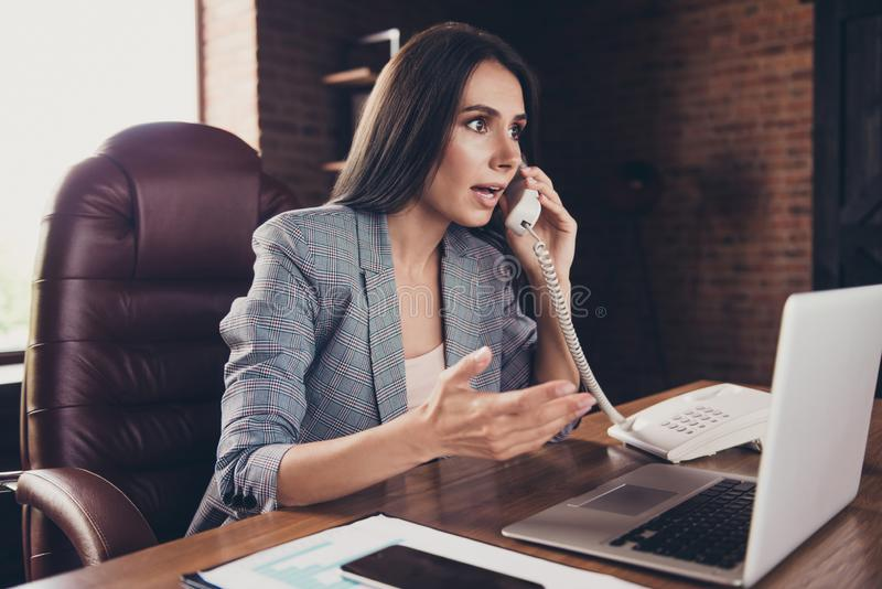 Elegant classic trendy stylish confused lady, wearing grey blaze. R, jacket, suit, speaking on phone, explaining, tense conversation at modern loft work place stock photos