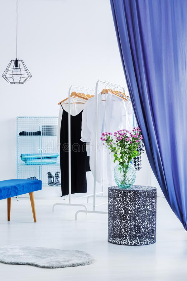 Elegant clothes in modern closet. Elegant clothes in white modern closet behind blue curtains royalty free stock photography