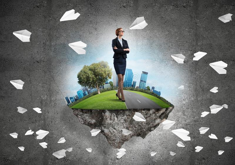 Confident lady boss and modern city as concept of eco green construction. Elegant confident businesswoman standing on green floating island against concrete stock illustration