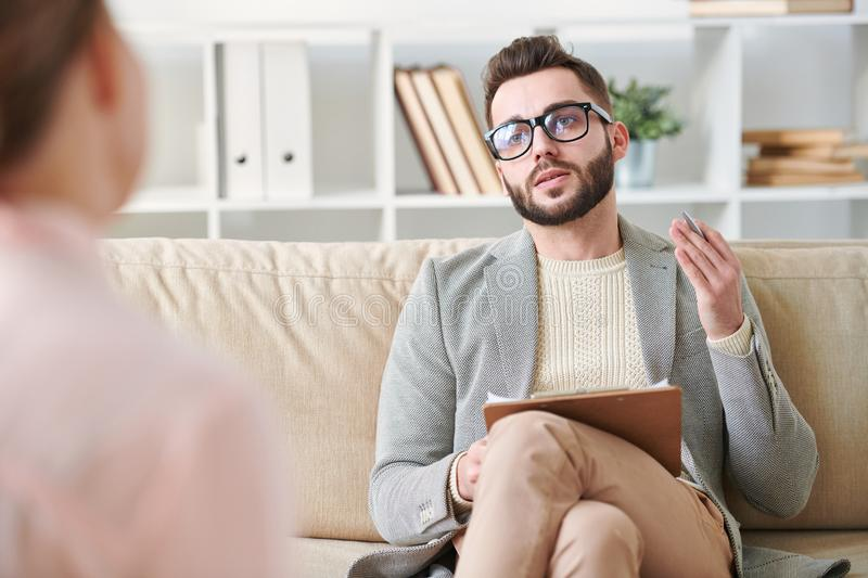 Elegant counselor. Young elegant professional counselor talking to one of patients while sitting on couch in front of her royalty free stock photos