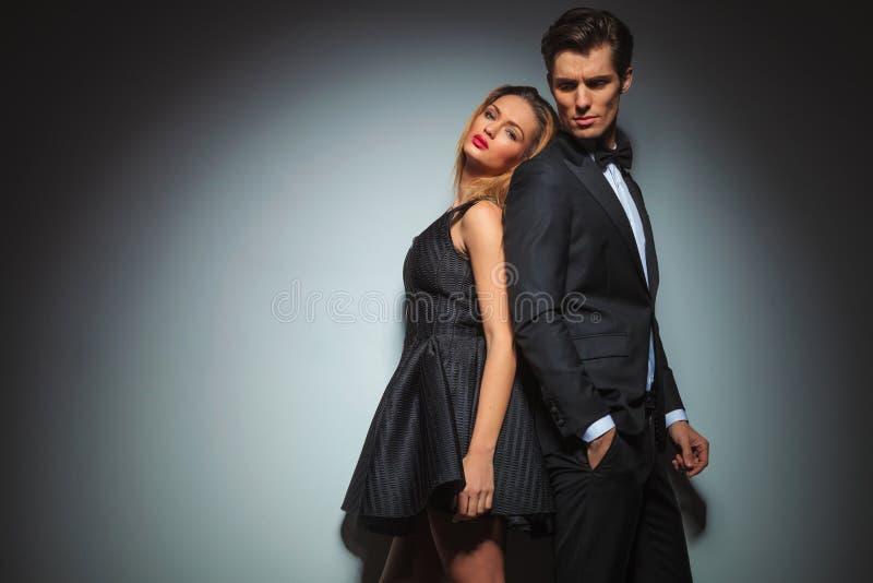 Elegant couple in black posing back to back royalty free stock photos