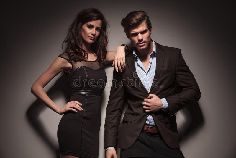 Elegant couple leaning on a dark grey wall stock photo