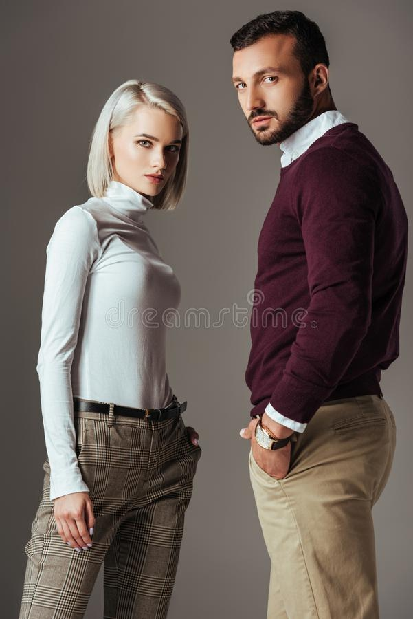 Elegant couple posing in autumn outfit. Isolated on grey stock photography
