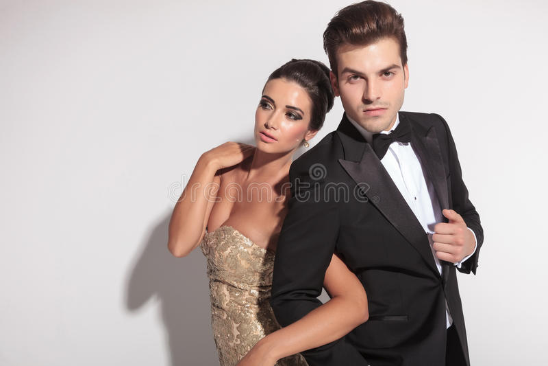 Elegant couple posing, holding each other arm. royalty free stock image