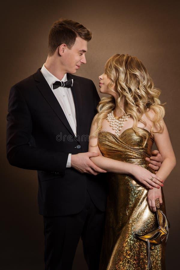 Elegant Couple, Vacker Fashion Woman i guldklänning, Elegant man i Tuxedo Suit fotografering för bildbyråer