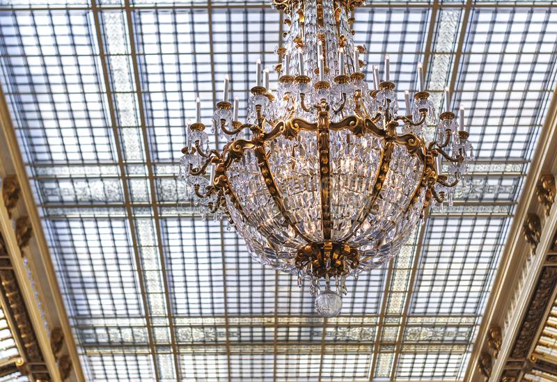 Elegant crystal chandelier. Hanging from a glass ceiling royalty free stock image