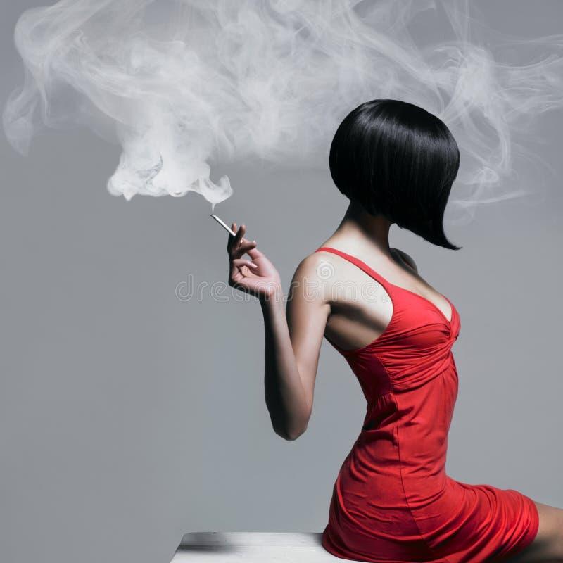 Elegant dam med cigaretten royaltyfria foton
