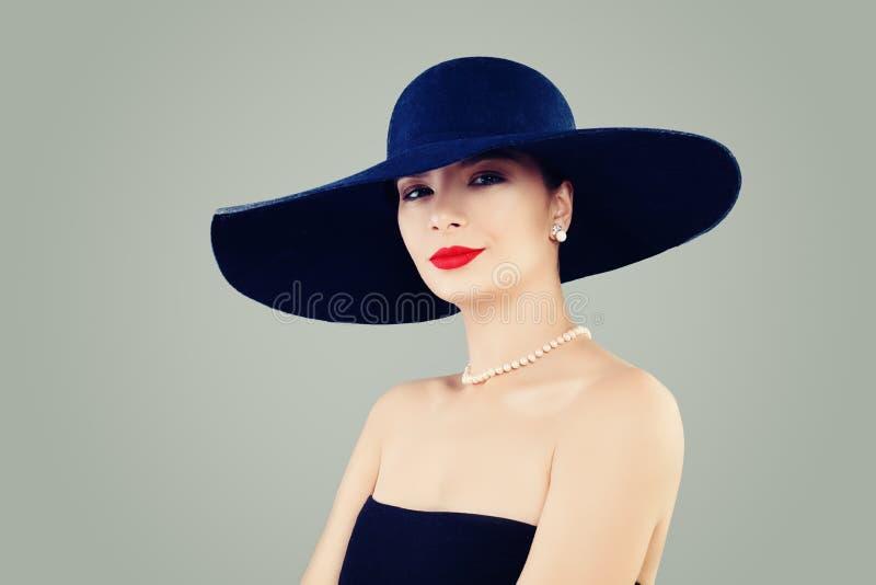 Elegant dammodemodell med röd kantmakeup, den klassiska hatten och vita pärlor royaltyfria bilder