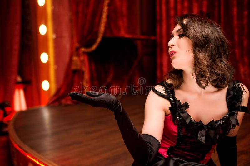 Elegant dancer in moulin rouge style sends an air kiss from the stage. Photo of Elegant dancer in moulin rouge style sends an air kiss from the stage royalty free stock photo