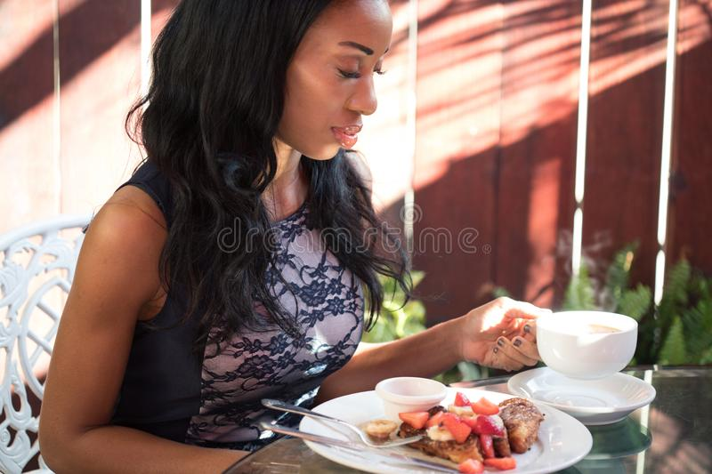 Elegant dark-skinned woman having breakfast on the terrace of a. Beautiful cafe royalty free stock photography
