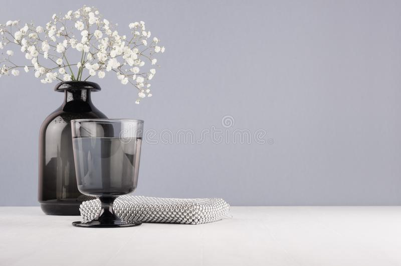 Elegant decor dressing table in minimalist style - black vase with flowers, glass, cosmetic accessories silver bag on grey wall. stock image