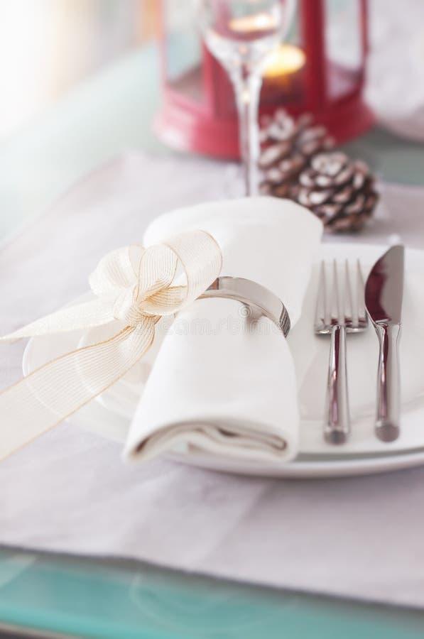 Elegant dekorerad jul bordlägger inställningen med moderna bestick-, servett-, pilbåge- och julgarneringar royaltyfri foto