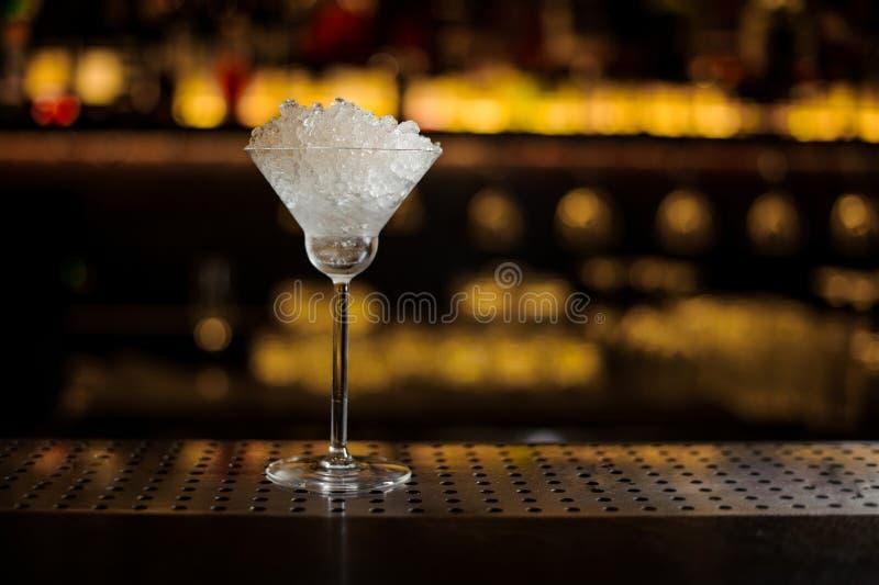 Elegant die cocktailglas met heel wat ijsstukken wordt gevuld royalty-vrije stock foto