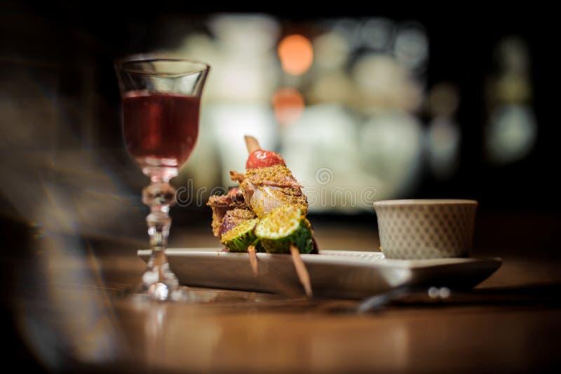 Elegant die glas met de smakelijke cocktail van Arnaud met een plaat van smakelijke schotel wordt gevuld royalty-vrije stock afbeeldingen