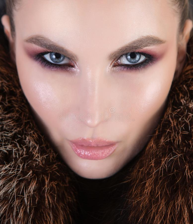 Elegant die portret van een meisje met sterk make-up en bont wordt geschoten royalty-vrije stock foto's