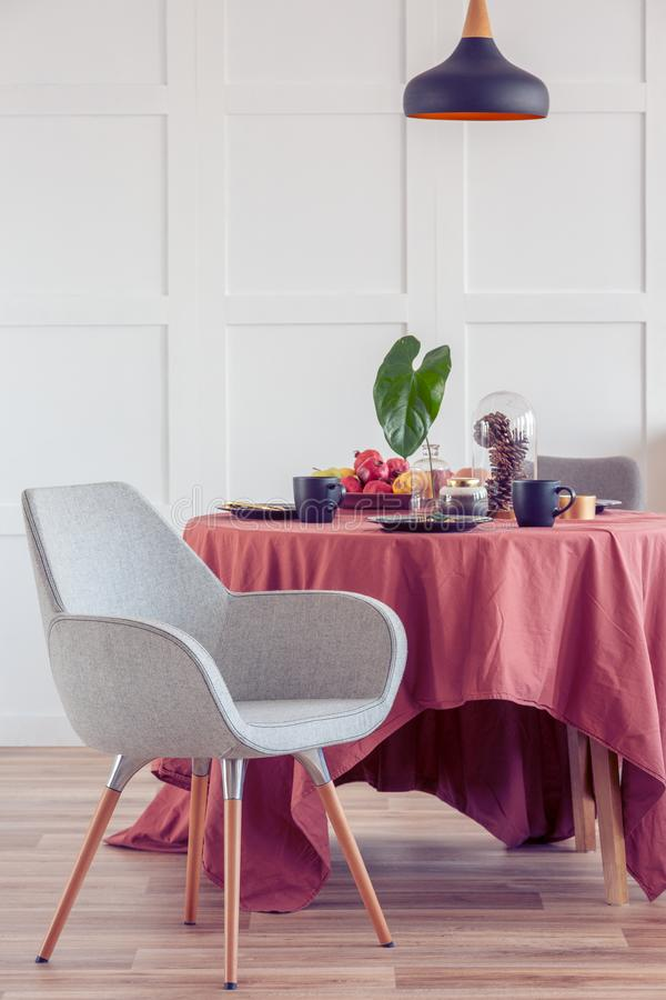 Elegant dining room table covered with ginger tablecloth in bright living room interior with stylish chairs stock photos