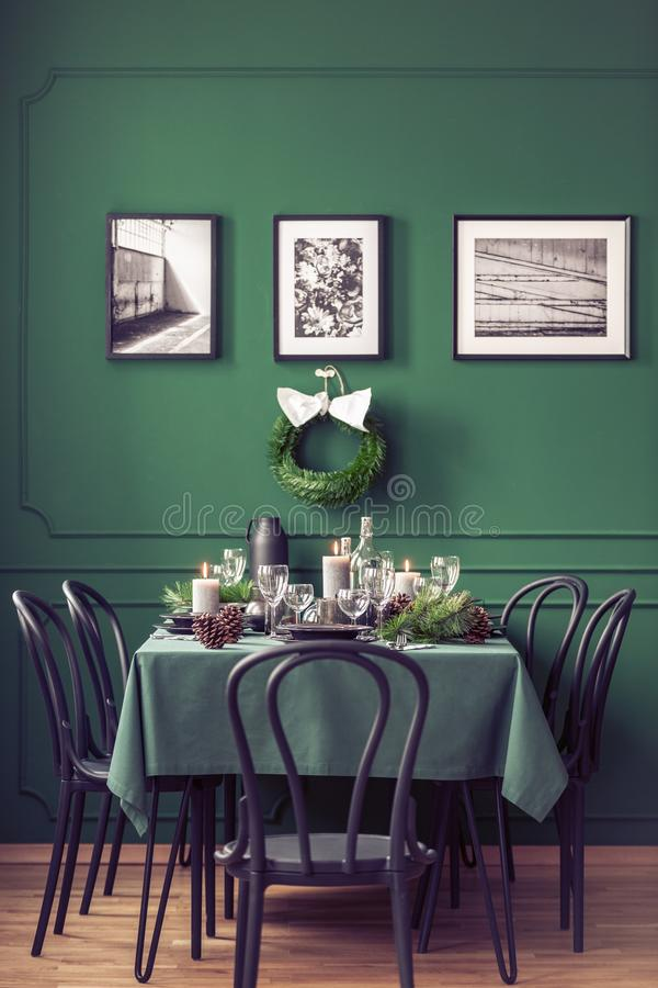 Elegant dining room table with wine glasses, plates and candles set for christmas dinner, gallery of black and white posters on stock photography