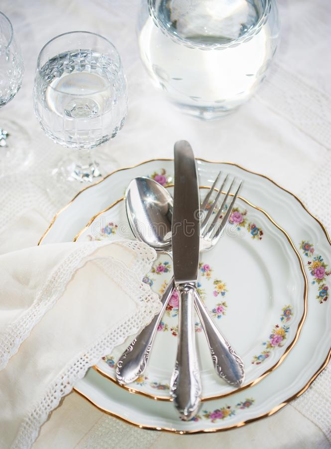Elegant dinner set with silver knife, fork and spoon lying across luxyry porcelain dishes, and crystal glassware on cream vintage royalty free stock photo