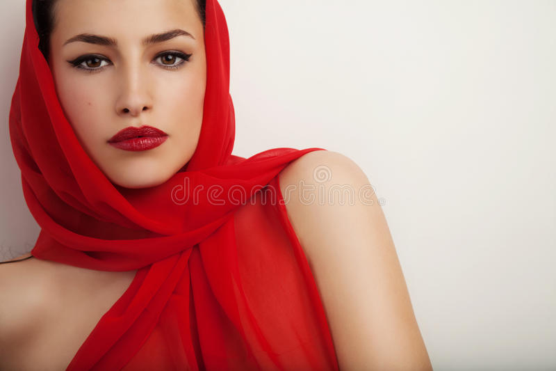 Elegant diva. Beautiful woman portrait with red lips and red veil over her head, studio shot royalty free stock photo