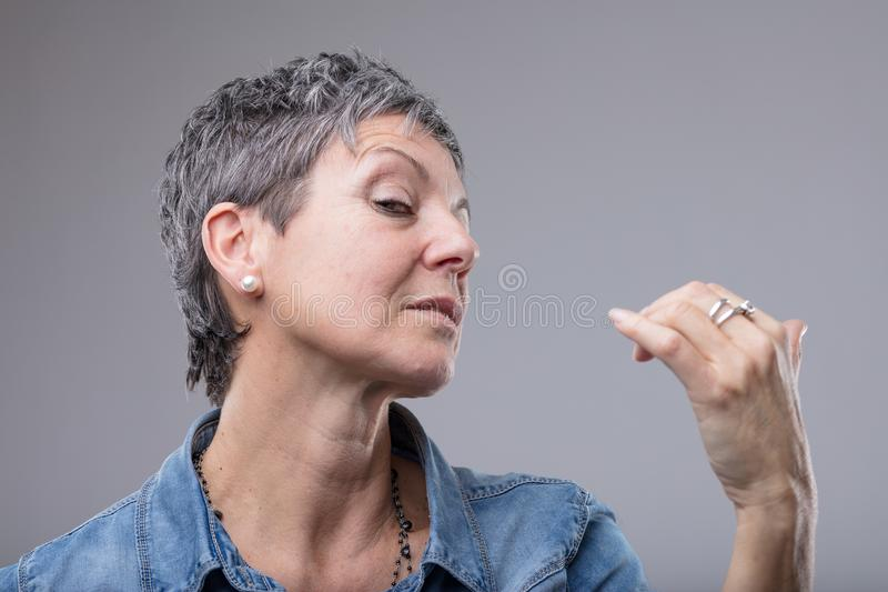 Elegant diva style woman with supercilious look. Glancing sideways at the camera as she gestures with her hand on grey stock image