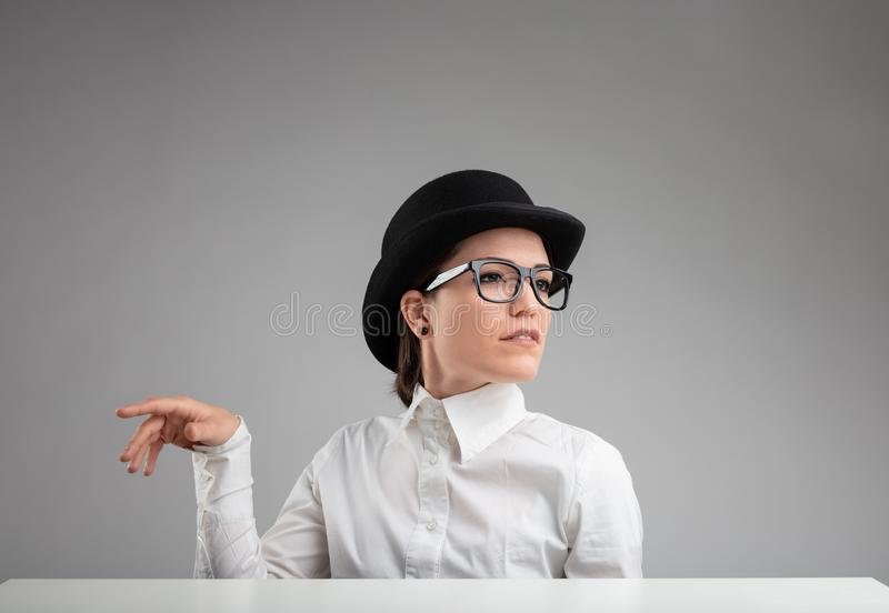 Elegant diva in a vintage bowler hat and glasses. Gesturing with her hand and looking off to the side with a superior proud expression against a grey background stock photos