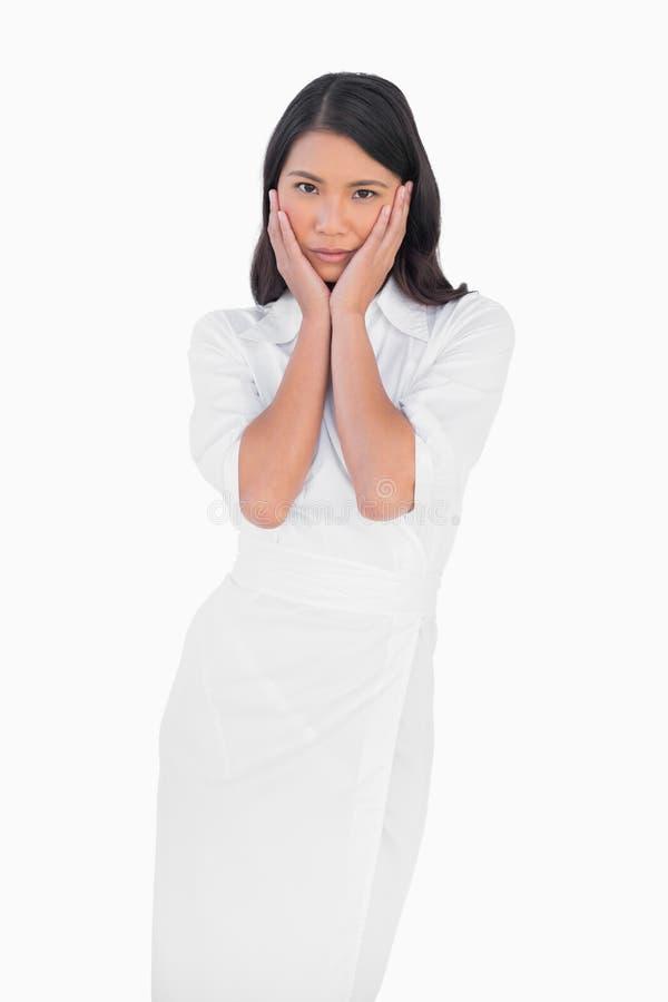 Elegant donker haired model die witte kleding wat betreft haar gezicht dragen stock foto