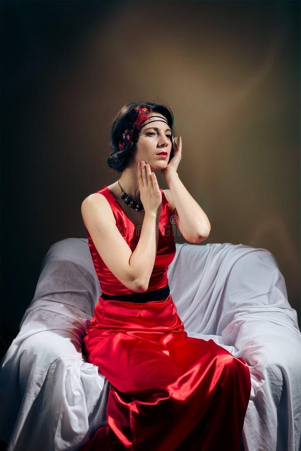 Elegant donkerbruin meisje in rode toga die spreken stock afbeeldingen