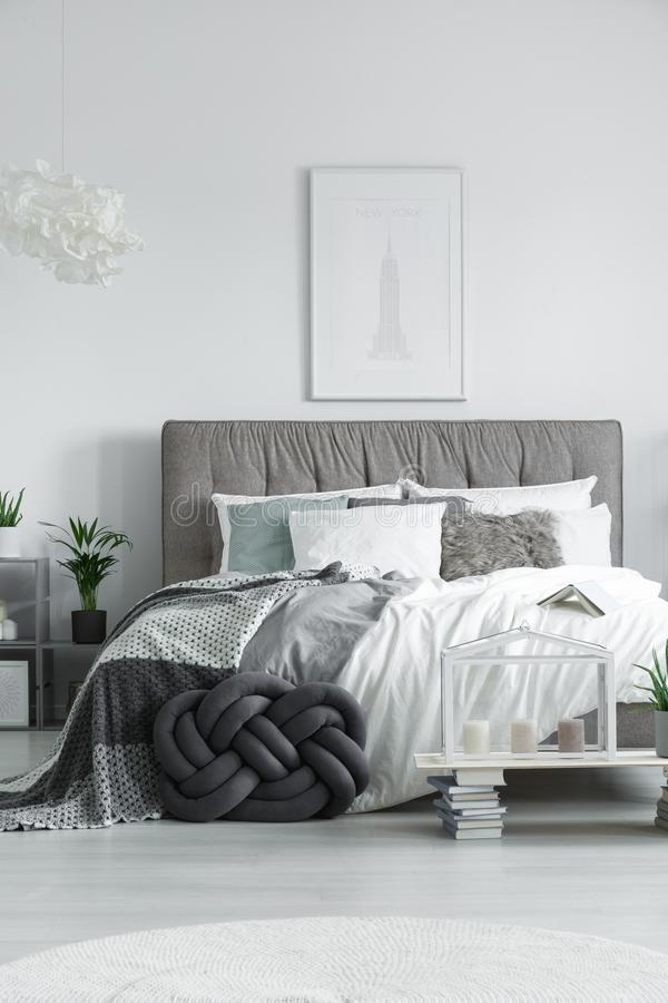 Elegant double bed with pillows. Elegant double bed with various pillows, and a set of candles standing on a small table made from books royalty free stock images
