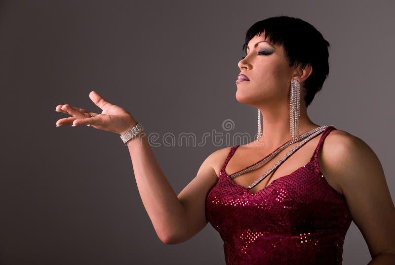 Elegant drag queen. Horizontal shot of an elegant Drag queen wearing a dark red velvet dress, holding her hand up to the light stock images