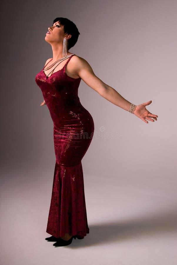 Elegant Drag queen. Full length shot of an elegant Drag queen wearing a dark red velvet dress, holding her arms out behind her stock images