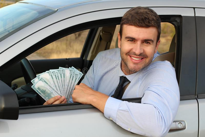 Elegant driver holding lots of dollars royalty free stock photos