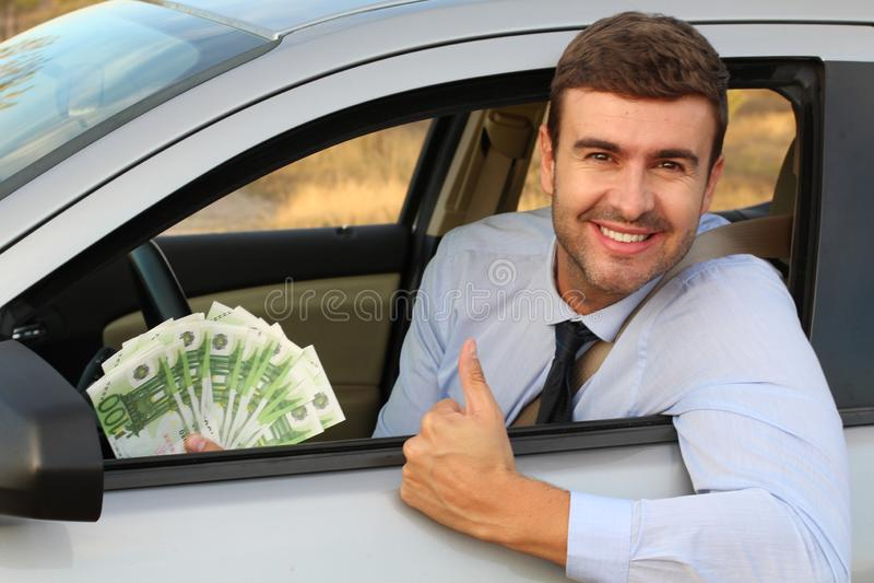 Elegant driver holding lots of money royalty free stock photo