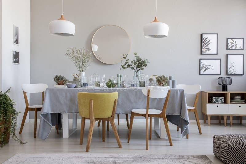 Elegant eetkamerbinnenland met een gelegde lijst, stoelen, spiegel op een muur en lampen stock afbeelding