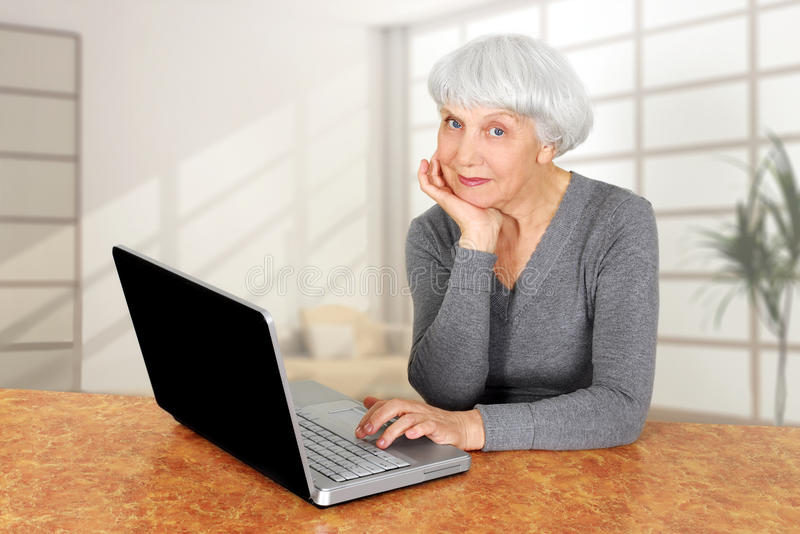 Elegant elderly senior woman using laptop computer communicates stock image