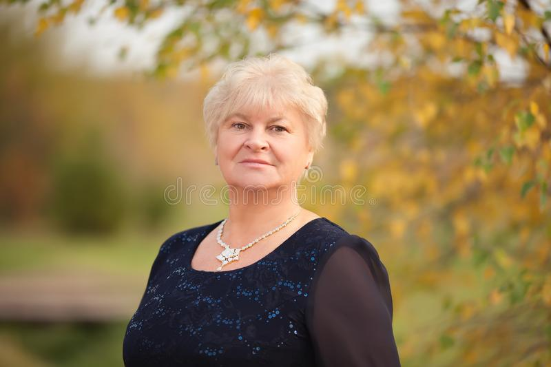 Elegant elderly woman portrait, autumn day. stock photo