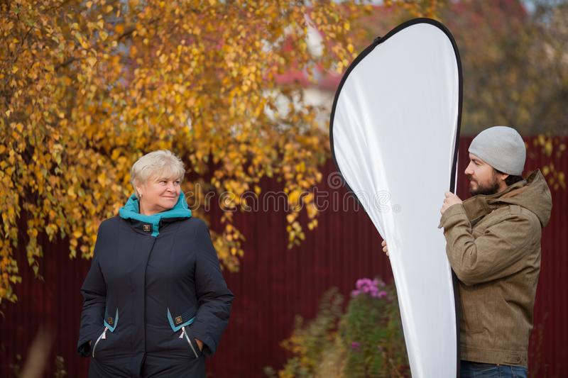 Elegant elderly woman posing to photographer, assistant holding reflector. stock photography