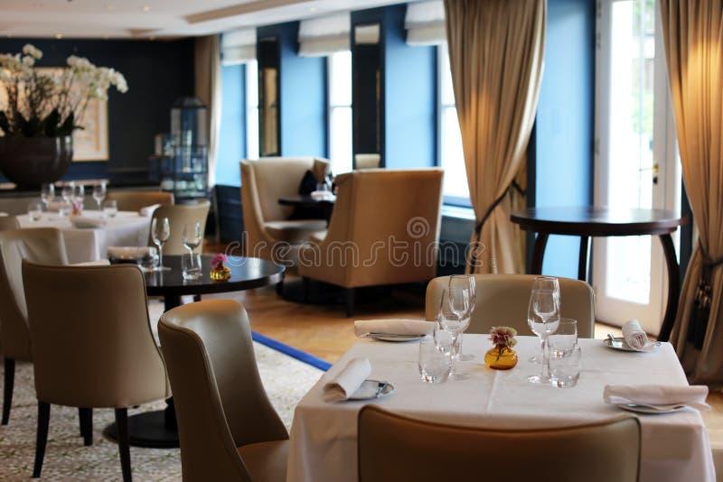 Elegant elegant en modern restaurant in Amsterdam, Nederland in Europa Zetels, lijsten en lampen bij het hotel van de luxepremie royalty-vrije stock afbeeldingen