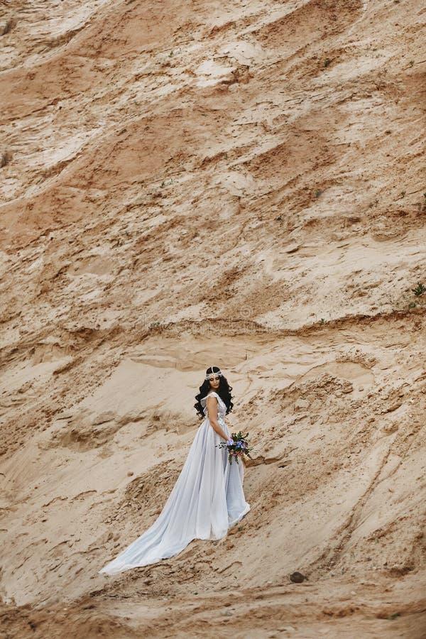 Elegant en modieus donkerbruin modelmeisje met juwelen op haar hoofd in het modieuze kantkleding stellen bij de zandige heuvel royalty-vrije stock afbeeldingen