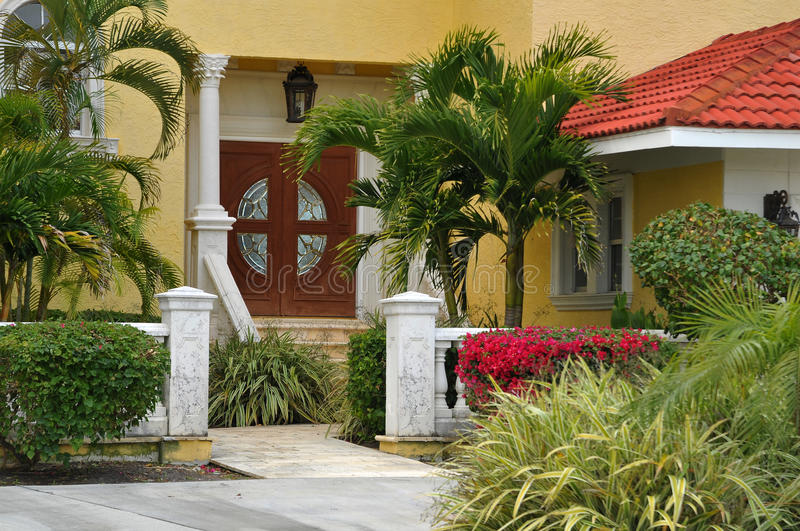 Elegant entrance to a luxurious home. Large, elegant home in Tropical Florida seated on a waterfront canal. Gorgeous landscaping leads vsitor to the double stock photography