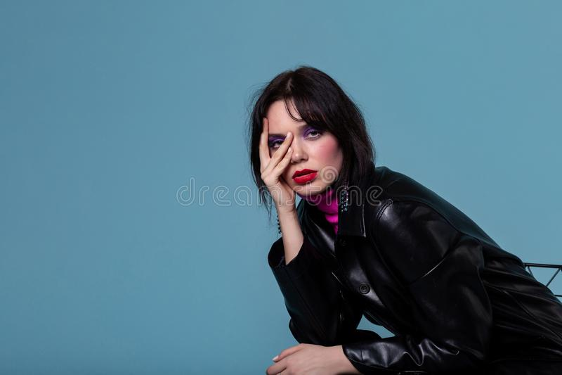 Elegant eoropean flicka med färgrik makeup som trycker på framsidan med fingrar och ser kameran royaltyfria bilder