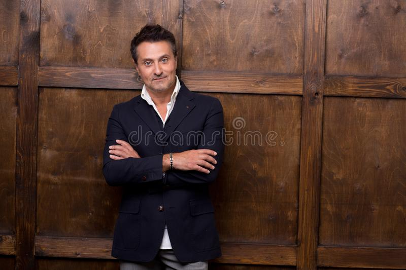 Elegant European man having his arms crossed and standing alone stock images