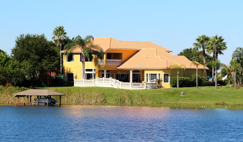 Elegant förorts- hus på sjön fotografering för bildbyråer
