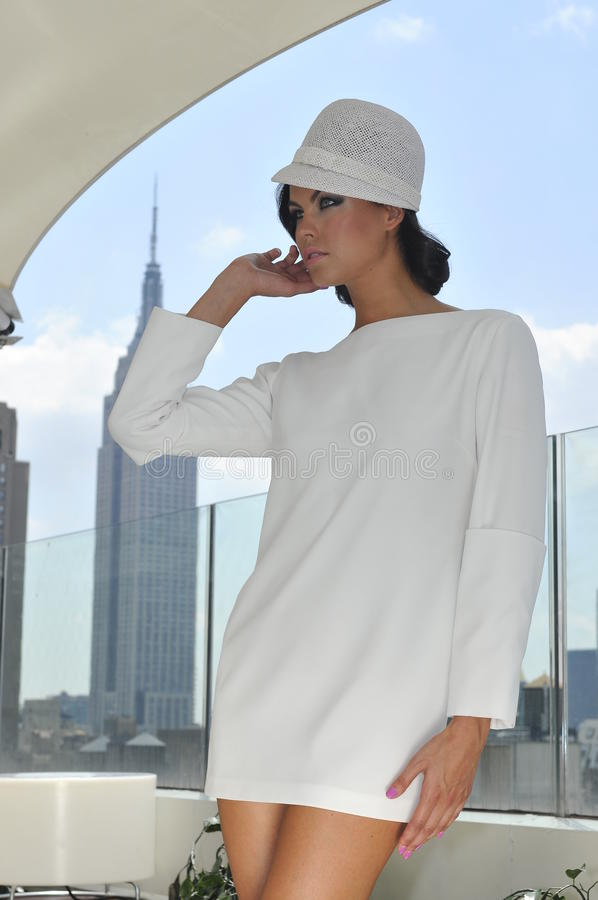 Elegant fashion model wearing couture white dress. And posing on the rooftop with city view on the background stock image