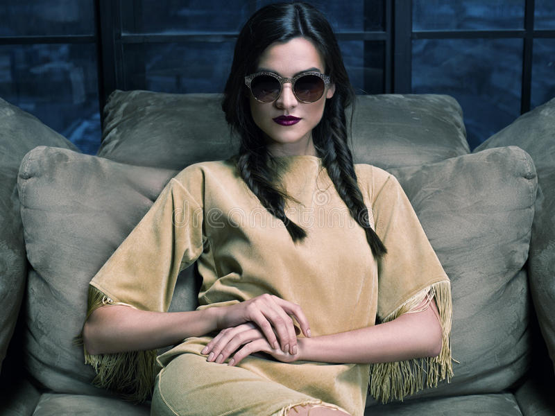 Elegant fashion model wearing mustard dress, sitting on the couch. Elegant fashion model wearing mustard dress and sunglasses, sitting on the couch in front of royalty free stock photos