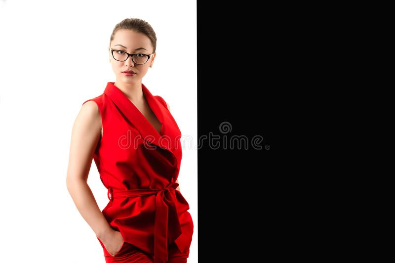Elegant fashionable business woman in red suit on black and white background royalty free stock images
